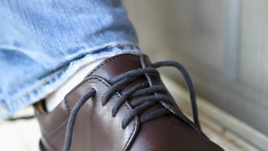 Close up of man tying his shoelaces in a bow.