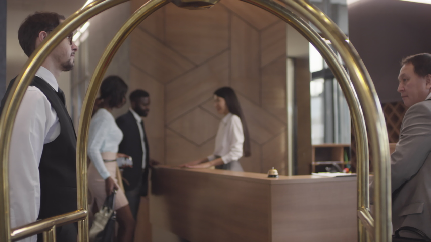 Tracking shot of professional hotel porter in glasses and uniform helping guests and putting their suitcases on luggage cart, then pushing it and leaving