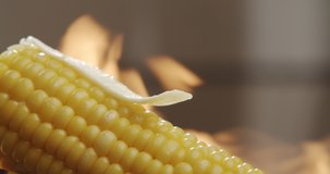 Piece of butter melts on hot corn with blazing fire in the background. Tasty young sweet corn. Slow motion video