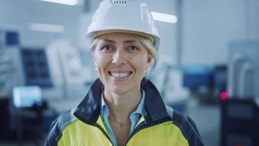 Portrait of Beautiful Smiling Female Engineer Wearing Safety Vest and Hardhat Takes of Safety Goggles. Professional Woman Working in the Modern Manufacturing Factory. Facility with CNC Machinery