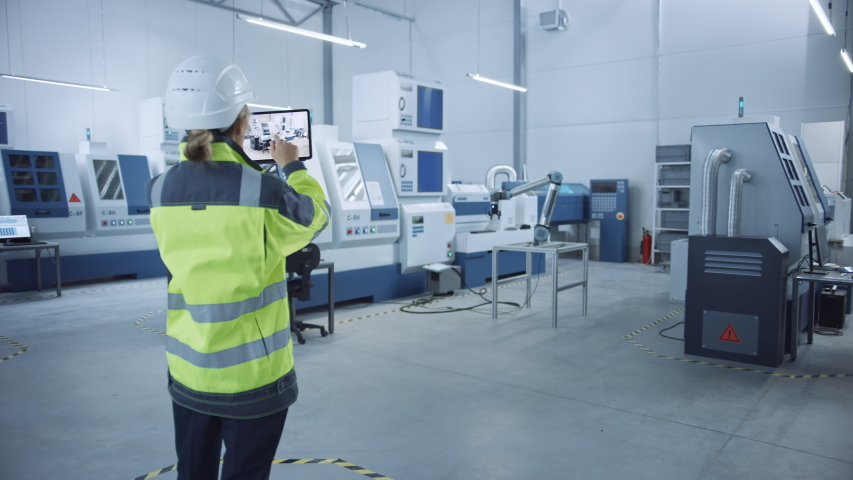 Industry 4.0 Modern Factory: Female Engineer Uses Digital Tablet Computer with Augmented Reality to Visualize Workshop Mapping, Floor Layout. Facility with High-Tech CNC Machinery and robot arm Royalty-Free Stock Footage #1045897897