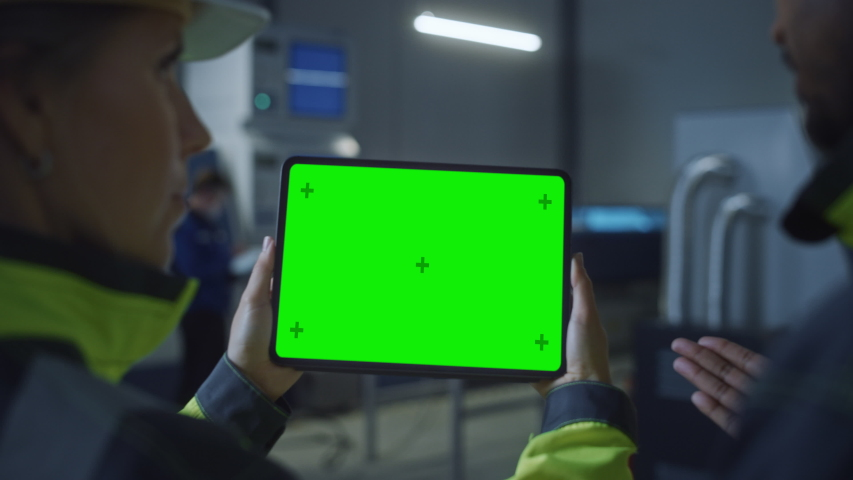 Industry 4.0 Factory: Chief Engineer and Project Supervisor in Safety Vests and Hard Hats, Talk, Use Digital Tablet Computer with Green Screen, Chroma Key. Workshop with Machinery. Zoom Out