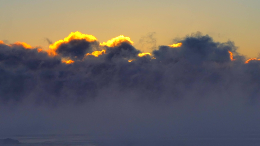 Massive clouds of Great Lakes fog backlit by the rising sun at twilight, seamless loop.