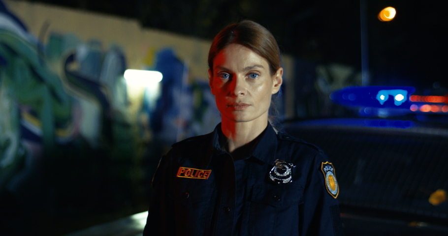 Portrait of attractive Caucasian young female police officer looking in car at night. Policewoman at the police car withh lights outdoor in dark. Quarantine coronavirus infection, protection