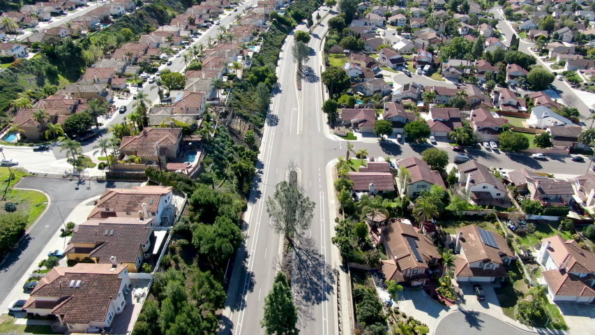 Aerial view of small road in typical suburban neighborhood with big villas next to each other during sunny day, San Diego, California, USA. Aerial view of residential subdivision house