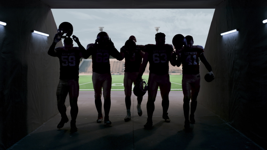 American football players walking through the stadium tunnel after team practice. 4K UHD,