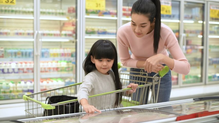 Shopping concepts. Mother and daughter are choosing to buy ice cream in the freezer. 4k Resolution. Royalty-Free Stock Footage #1045963033