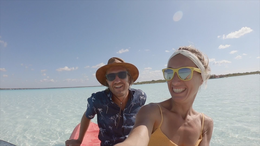 Happy young couple on canoe in Mexico taking selfie portrait. Two people bonding and having fun in tropical climate kayaking. SLOW MOTION