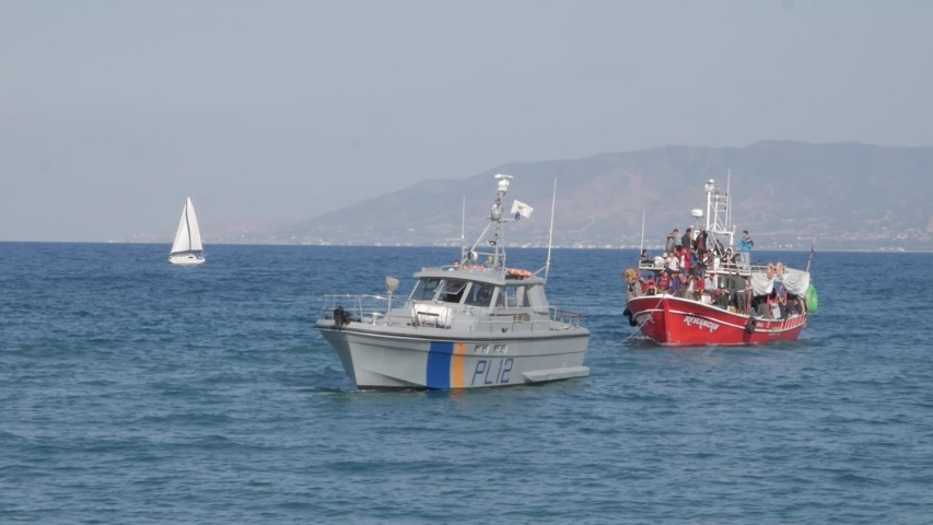 Latchi Polis Chrysochou / Cyprus - 11 04 2019: Wide shot of a boat full of illegal immigrants from the Syrian war being pulled into shore by the coastguard at Latchi Polis Chrysochou, Cyprus on Novemb
