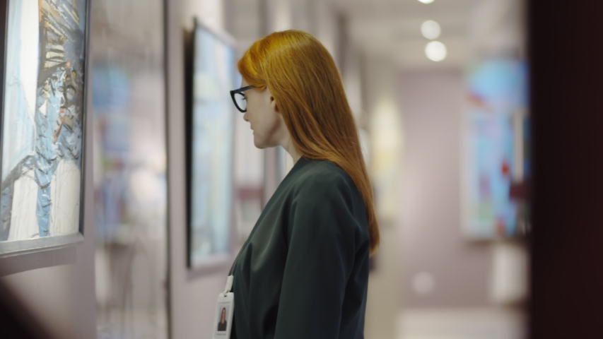Thoughtful female gallery visitor in glasses standing beside wall in exhibition hall, looking at painting and admiring artworks Royalty-Free Stock Footage #1046009308
