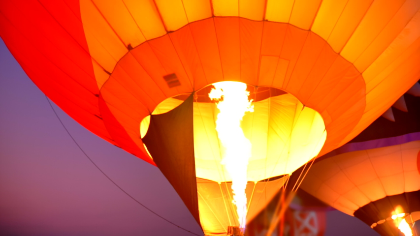 Scene slow motion of flame rising and inflating hot air balloon