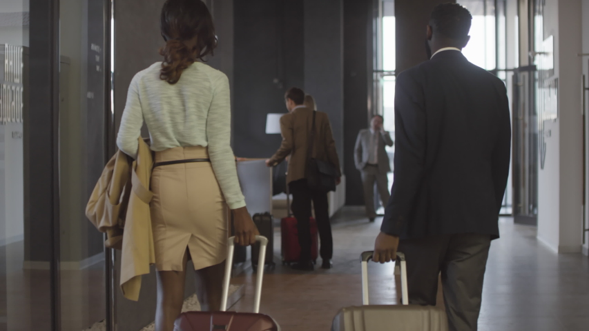 Tracking of man and woman with suitcases walking up to reception desk and giving their passports to cheerful female receptionist while checking out of hotel