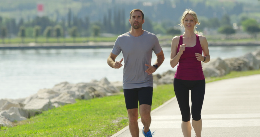 4K Slow Mo Of Man And Woman Jogging Harmoniously By The Seaside | Shutterstock HD Video #1046018938