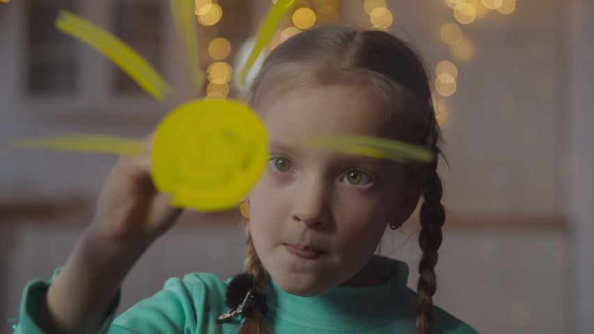 Lovely elementary age girl with pigtails painting sun on window glass with paintbrush and yellow paint at home. Positive little artist drawing on window, expressing her imagination and creativity. Royalty-Free Stock Footage #1046023927