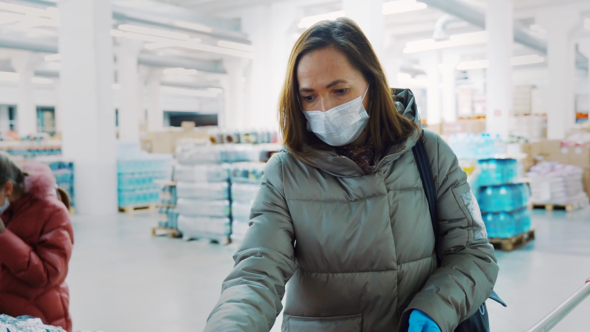 A woman with a daughter in winter clothes and in medical masks in the store buying dried prunes, dried fruits. | Shutterstock HD Video #1046024470