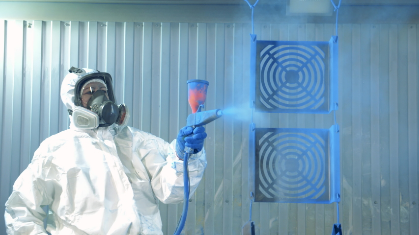 Industrial painting process at painting factory facility. Technician in safety wear is dying metal pieces blue Royalty-Free Stock Footage #1046030266