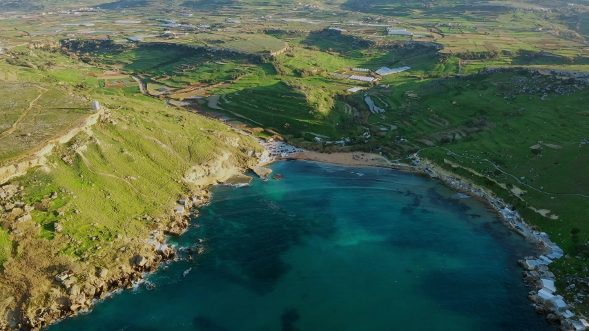 Aerial view of Gnejna bay beach. Winter, a lot of greeny, hills and fields, blue sea. Malta island