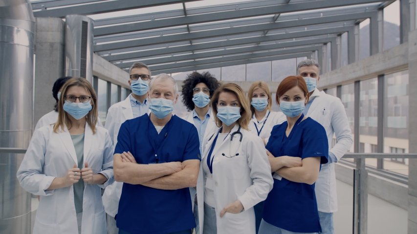 Group of doctors with face masks looking at camera, corona virus concept. Royalty-Free Stock Footage #1046043454