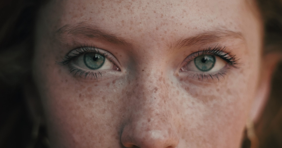 Close up of Woman's Face, Girl opening her Beautiful blue azzure Eyes, Attractive Ginger. Natural Beauty with Freckles. Gorgeous woman with long Eyelashes and Attractive Appearance. Slow motion. #1046054536