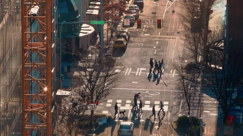 Seattle, Washington - Feb 2, 2019: Seattle crosswalk in the evening on a sunny winter day. golden and blues. long shadows. cars stopped waiting for pedestrians on crosswalks.