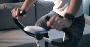 Close up of fitness woman in sport clothing exercising legs on static bike and wearing smart watch for measuring blood pressure. Concept of control and responsible attitude for health status