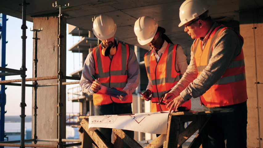 Three engineers work with a blueprint in a building. Construction contractor working on a construction site. | Shutterstock HD Video #1046079055