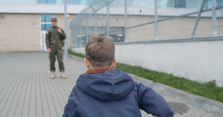 Happy son with toy and american flag running to his military father embrace. Child hugging excited soldier father. Concept of military service and long awaited meeting. Happy famiilly reunion