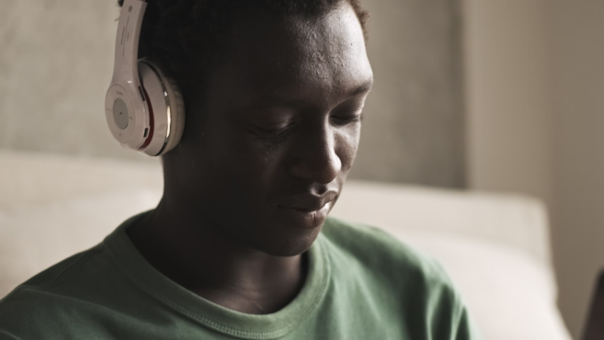 A close-up view of a calm young african american man with wireless headphones is listening to the music in the living room at home