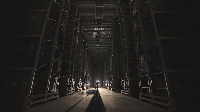 The beginning of the working day at the factory, men walk through the warehouse with a trolley | Shutterstock HD Video #1046092399