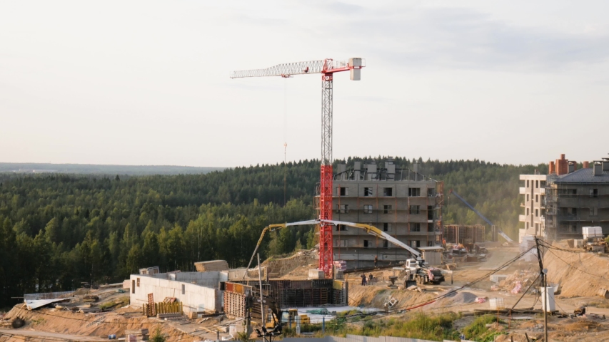 Aerial panoramic time lapse of construction site of suburban houses with white red tower crane, truck crane, concrete mixer, concrete feed truck and tractor in the green valley and trees