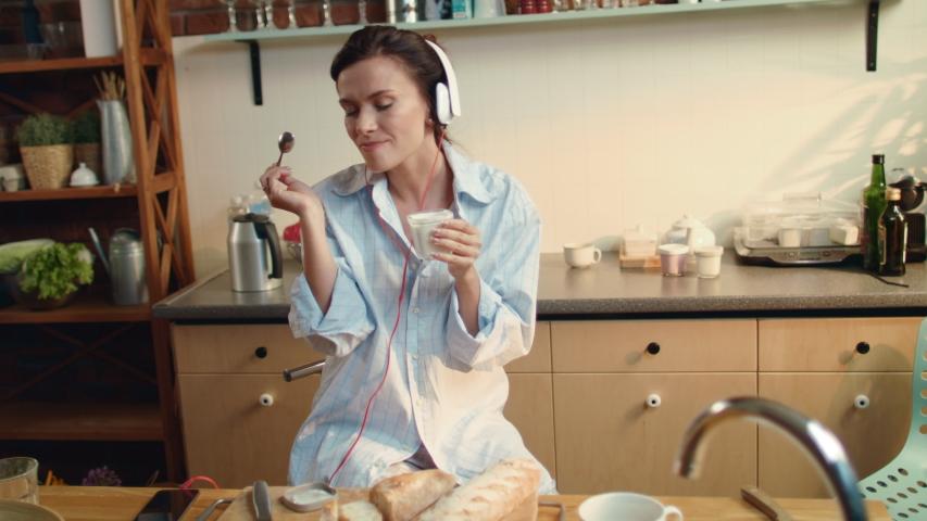 Attractive woman in headphones eating yogurt in kitchen. Beautiful girl listening music in headphones at breakfast time. Pretty brunette having yogurt for breakfast at kitchen table.