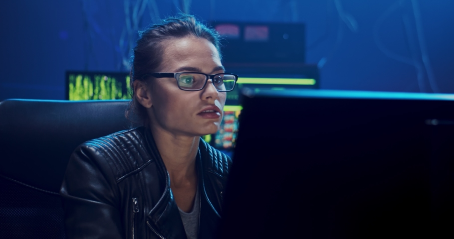 Caucasian young attractive female software developer working over some virus while sitting at the two computers screens in the dark room and programming.