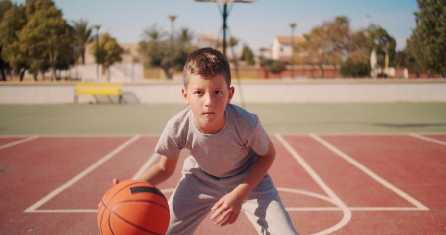 Cute kid hiting a basketball ball. Boy practicing shooting a basketball.