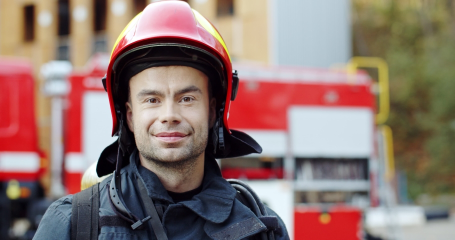 Close up of the young caucasian handsome fireman in the helmet turning face to the camera and smiling. Outdoors. Portrait.