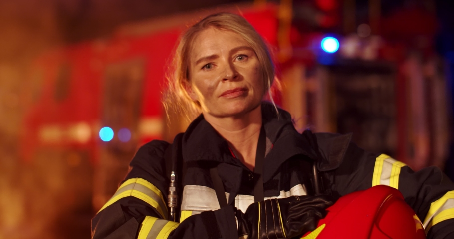 Portrait of the Caucasian tired female firefighter with the helmet in hands looking to the camera with a big fire truck on the background at night. Rescuer concept . Shot on Red Dragon  Royalty-Free Stock Footage #1046145100
