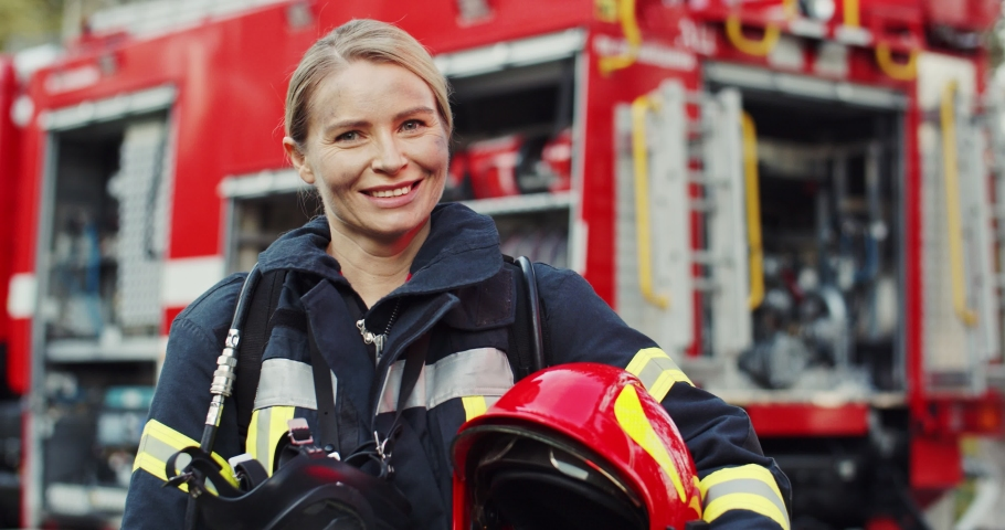 Portrait shot of the happy Caucasian young woman firefighter with the helmet in hand smiling to the camera after fire at the red truck. Outside. Royalty-Free Stock Footage #1046145193