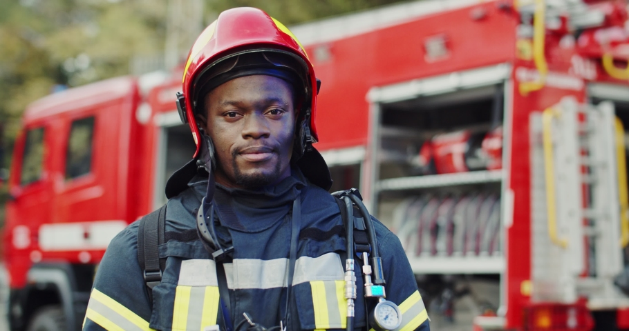 Portrait shot of the African American joyful firefighter taking off helmet and smiling to the camera at the big red truck after fire. Royalty-Free Stock Footage #1046145196