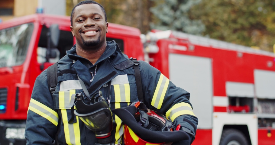 Portrait of the young joyful good looking African American fireguard taking off helmet and looking to the camera with a smile at the fire truck. Outdoors. | Shutterstock HD Video #1046145256