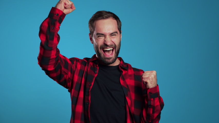 Yes winner gesture. Happy european man rejoices. Handsome guy with stylish beard surprised to camera over blue background.