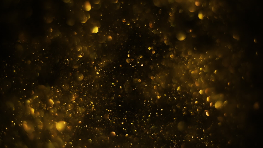 Golden glitter background in slow motion. Beautiful transition with real gold particles flying in wind on black background, shot with depth of field. Gold dust bokeh abstract background