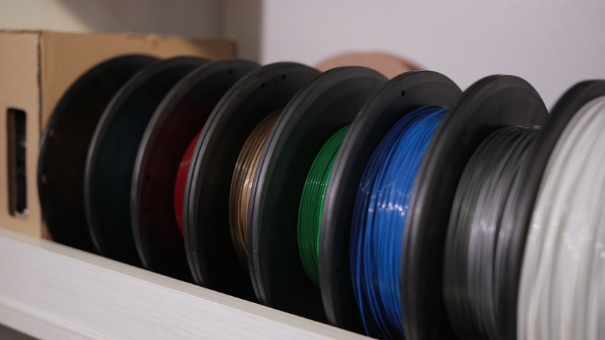 spools with a plastic thread cable for color printing sorted on the shelf 3D printer technology