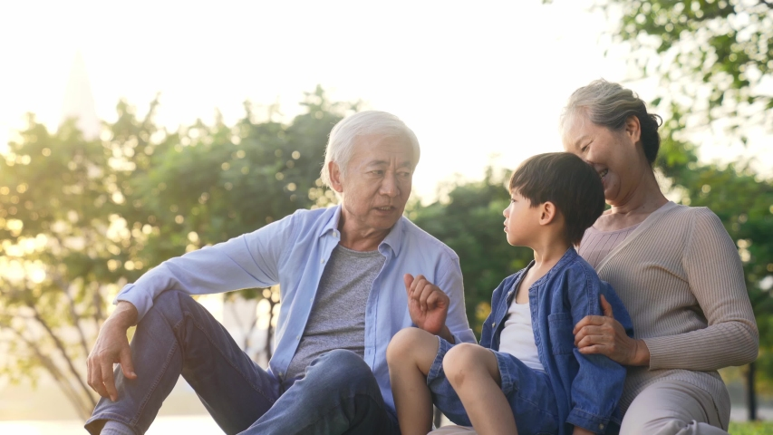 Happy senior asian couple sitting on grass having fun with grandson outdoors in park