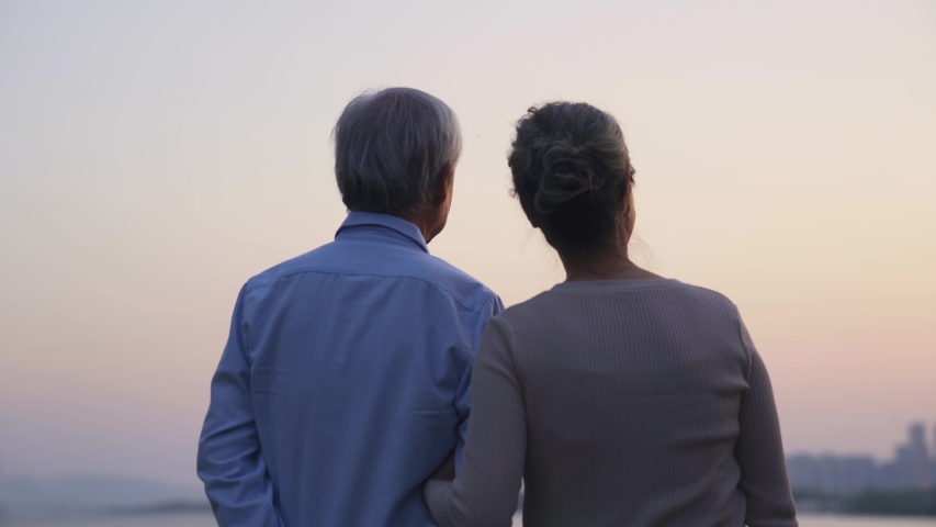 Rear view of loving asian senior couple standing by a river looking at sunset