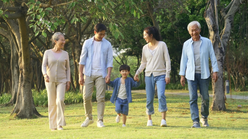 Happy multi generation asian family having a good time walking in park