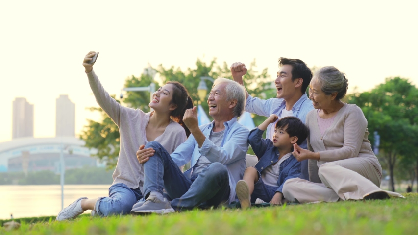 Happy three generation asian family sitting on grass outdoors taking a selfie