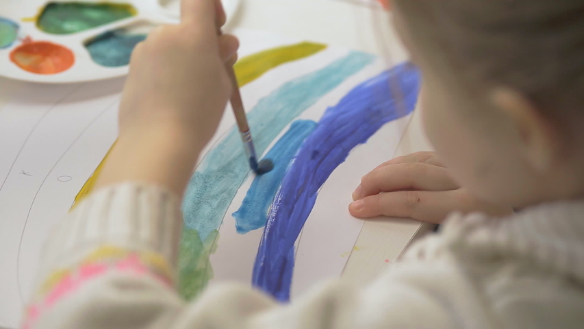 The left-handed girl draws a rainbow with watercolor paints and brushes, children's joint creativity.