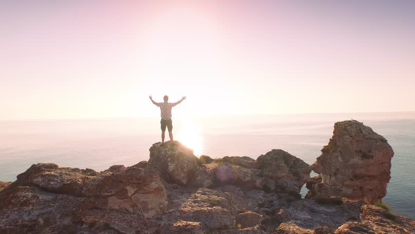 Young Man Vacation Happiness Standing On Top Of Sea Cliffs Raising Arms Joy Holiday Concept    Shutterstock HD Video #10461770