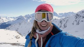 Happy young woman on ski slopes taking a selfie portrait on top of snowcapped mountains in winter enjoying ski season vacations. Girl having fun in Switzerland sharing selfie to friends video