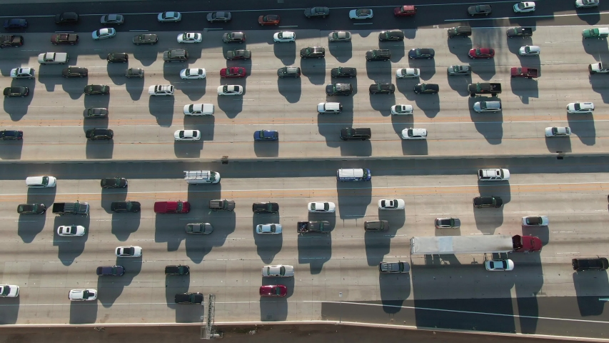 Aerial view from above of cars and trucks traveling in congested road traffic on the I-405 freeway in urban Los Angeles, California. | Shutterstock HD Video #1046183905