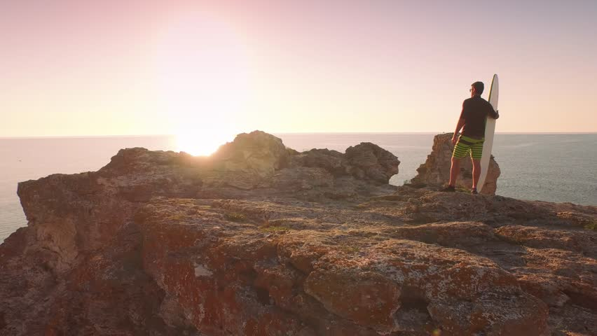 Surfer On Cliffs Rocks Wetsuit Sun Shine Sunset Ocean Beauty Vacation Holiday Concept Relaxation Sports Fit Healthy    Shutterstock HD Video #10461872